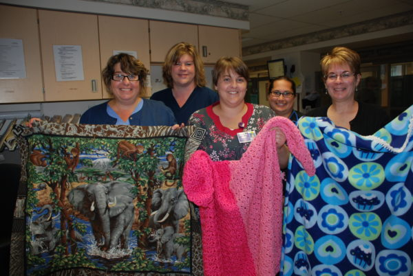 (left to right) Wayne Memorial staffers Lori Abraham, RN, Chandra Roberts, RN, Kimberly Donat and Jennifer Hoover-Hiza, RN are shown with Holly Hubert, chapter coordinator, Project Linus of Wayne County PA, holding handmade blankets designed to provide security, warmth and comfort to children in need.  Project Linus is one of eight organizations to recently receive grant funds from Wayne Memorial Health Foundation.