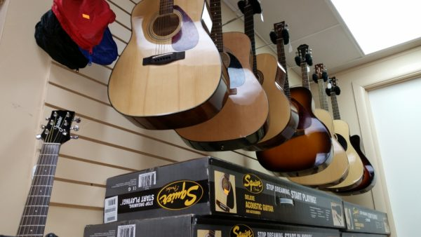 Fresh stocks. Acoustic guitars, some displayed from the wall and others still in their boxes, on sale at Big Bug Music in Stroudsburg.